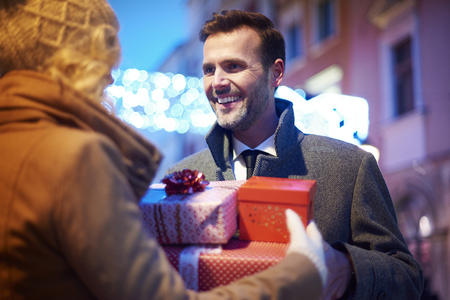 Mature man receiving full of presents from  woman