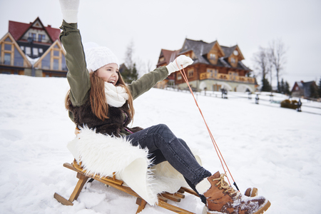 Girl with hands raised on a sleigh Stock Photo