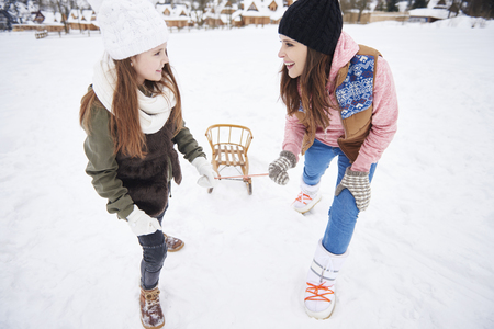 Mummy and daughter pulling sled together Stock Photo