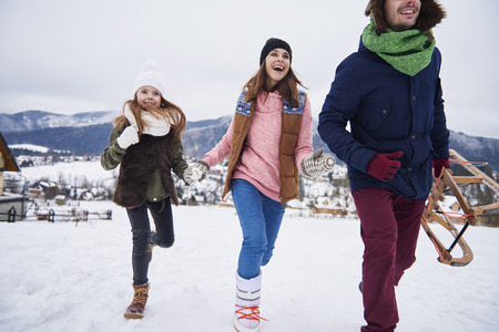 Family running through the snowy hills  Stock Photo