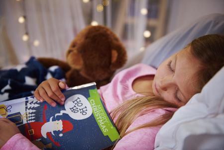 本とテディベアと昼寝をして小さな女の子 写真素材