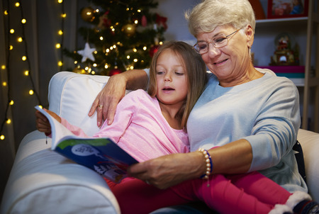 Grandmother and grandaughter in armchair with book Stock Photo