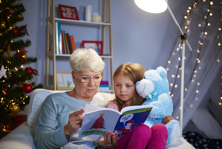 Christmas evening with grandmother, storybook and teddy bear