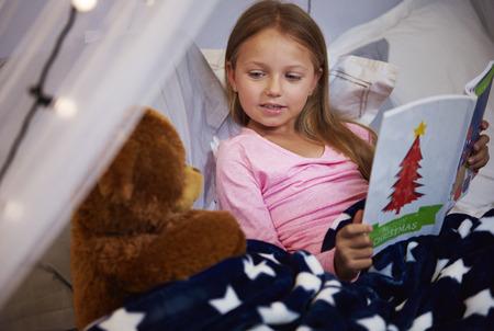 彼女とテディベアの童話を読んでいる女の子