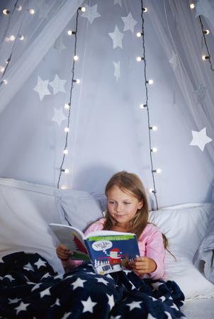 ベッドの上で本を読んでいる女の子 写真素材