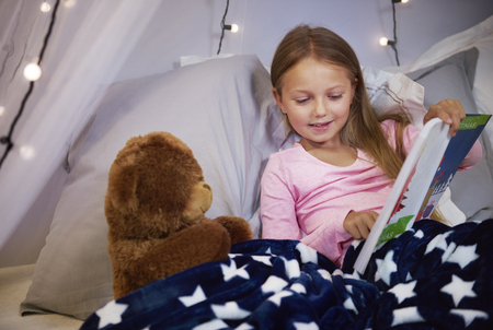 Girl watching a picture book with a teddy bear