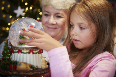 Senior with girl watching christmas snow globe
