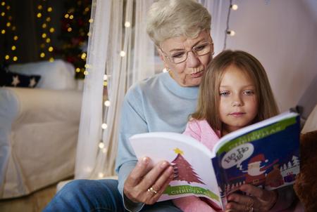 祖母と孫娘のベッドで絵本を読んで 写真素材