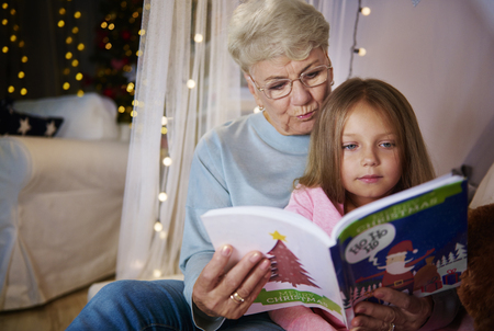 Grandmother and granddaughter reading storybook in bed Banco de Imagens