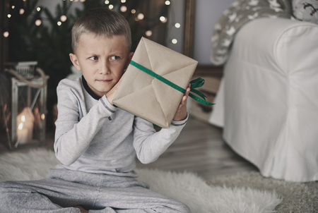 Boy shaking a wrapped present 版權商用圖片 - 86991260