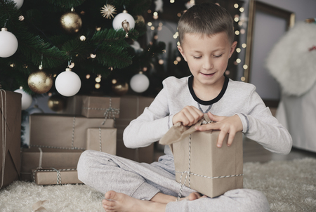 Child tearing a christmas paper  Stock Photo