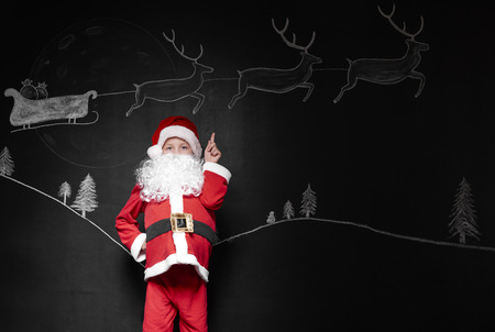 Child in santa claus costume pointing at background Stock Photo