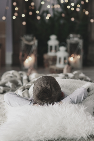 床に横になっている頭の後ろで手を持つ少年