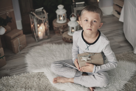 Boy with a gift squatting on rug at home Zdjęcie Seryjne