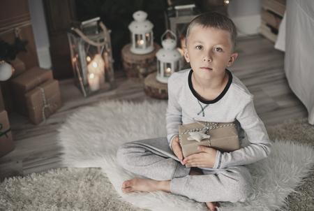 Junge mit einem Geschenk, das zu Hause auf Wolldecke hockt Standard-Bild - 86991294