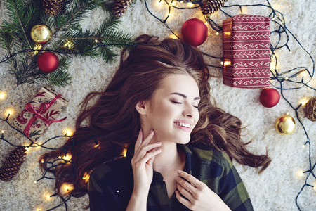 Woman surround by christmas lights lying on floor and dreaming