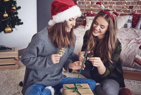 decorating: Sisters packing gifts in bedroom Stock Photo
