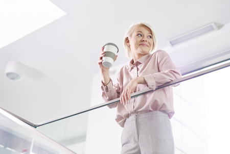 Cheerful businesswoman with mug of coffee leaning on a railing Imagens