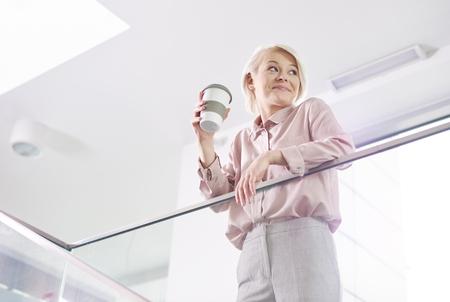 Vrolijke zakenvrouw met mok koffie leunend op een reling