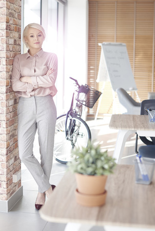 Het portret van gemiddelde lengte van onderneemster die zich in bureau bevindt Stockfoto