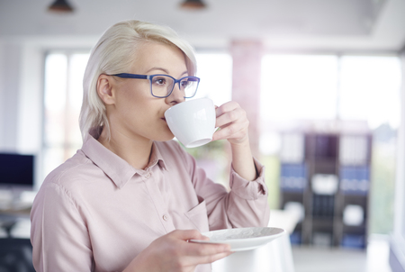 company: Woman drinking coffe at office