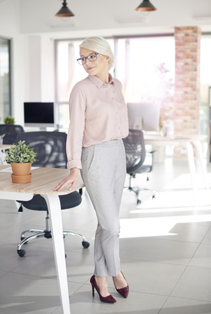 company: Business person leaning on office desk Stock Photo