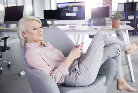 company: Barefoot businesswoman lying on armchair with mobilephone