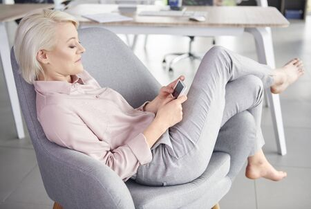 company: Barefoot woman with mobile phone relaxing Stock Photo