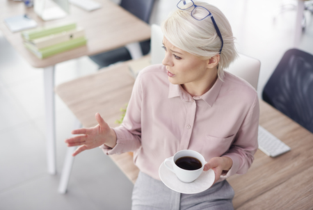 Businesswoman talking and gesturing while coffee break