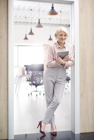 Glimlachende eigenaar die van bureau zich in deuropening bevindt