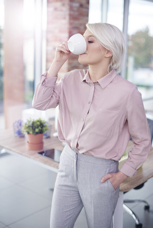 company: Woman with hand in pockets having a coffee Stock Photo
