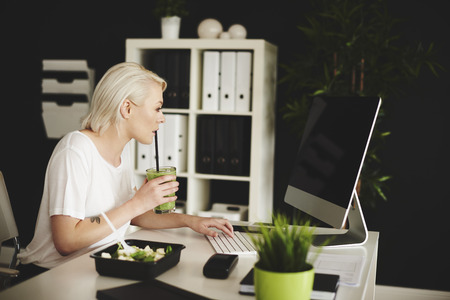 Woman drinking smoothie and working with a computer
