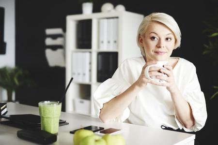 Thoughtful woman sitting at desk and holding mug