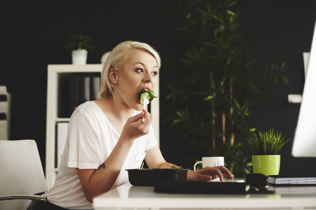 Multipurpose woman eating and using a computer at office Stock Photo