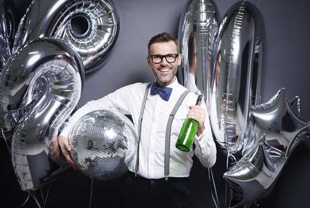 Man with disco ball and bottle of champagne  Imagens