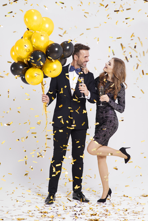 Couple with balloons and champagne flute celebrating new year