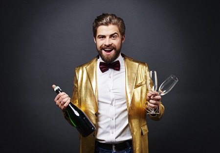 Cheerful man holding bottle of champagne and champagne flute Stock fotó