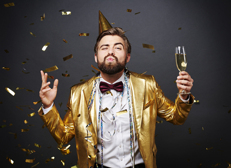 Man with champagne blowing lips