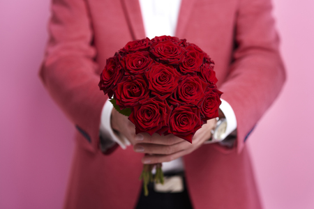 Unrecognizable man giving bunch of rose  Фото со стока