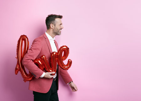 Cheerful man helping to preparing decorations for valentines party   Stock Photo