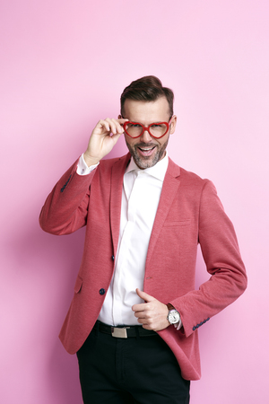 Cheerful man with heart shape eyeglasses posing