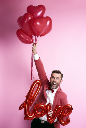 Funny man holding bunch of balloons heart shape