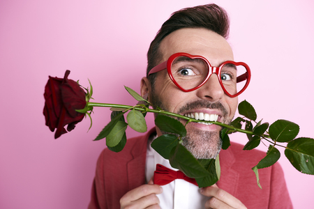 Man holding a rose in mouth