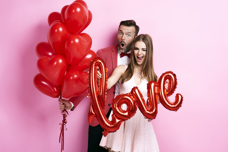 Man with balloon embracing his girlfriend Imagens