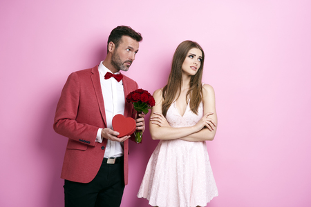 Man with bunch of rose and chocolate box apologizing fiancée