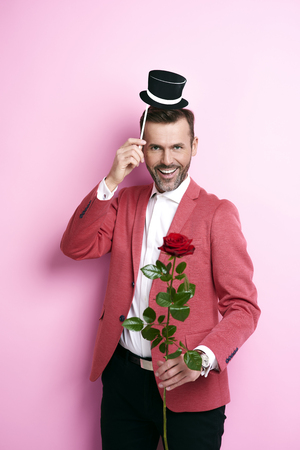 Man in red suit giving a rose  Stock Photo
