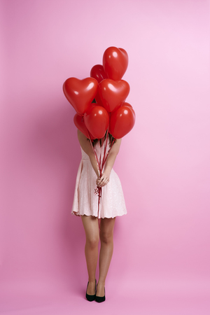 Woman holding bunch of heart shape balloons Stock Photo