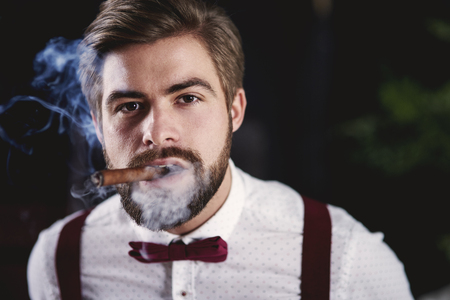 Front view of handsome man smoking cuban cigar
