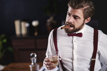 Portrait of handsome man with cuban  cigar and whiskey