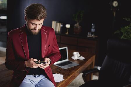 Smart businessman using smartphone while a short break  Banco de Imagens